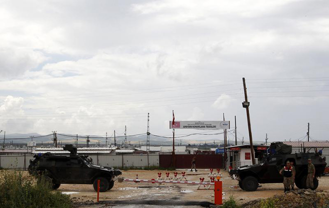Turkish soldiers with armored vehicles guard the entrance of Apaydin refugee camp in Hatay province, on the Turkish-Syrian border on May 12, 2013. © 2013 Reuters