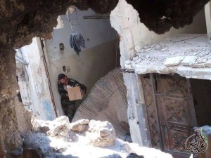 A soldier of the Syrian Army steals the contents of a house