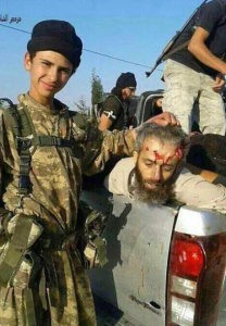A child holds the head of the Judge of Suqoor al-Shaam following his slaughter by ISIS