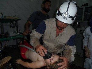 A paramedic trying to rescue a child, injured during the raid on Sarmin