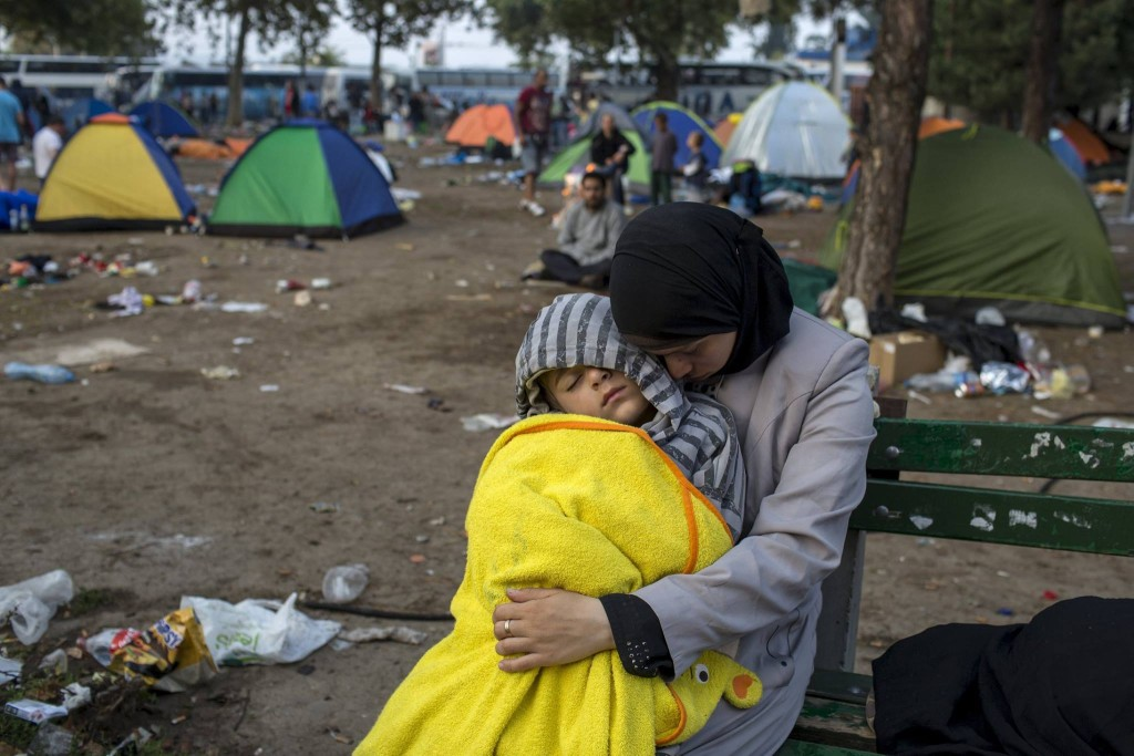 A migrant with a child sleeps in a park near the main bus and train station in Belgrade, Serbia, August 26, 2015