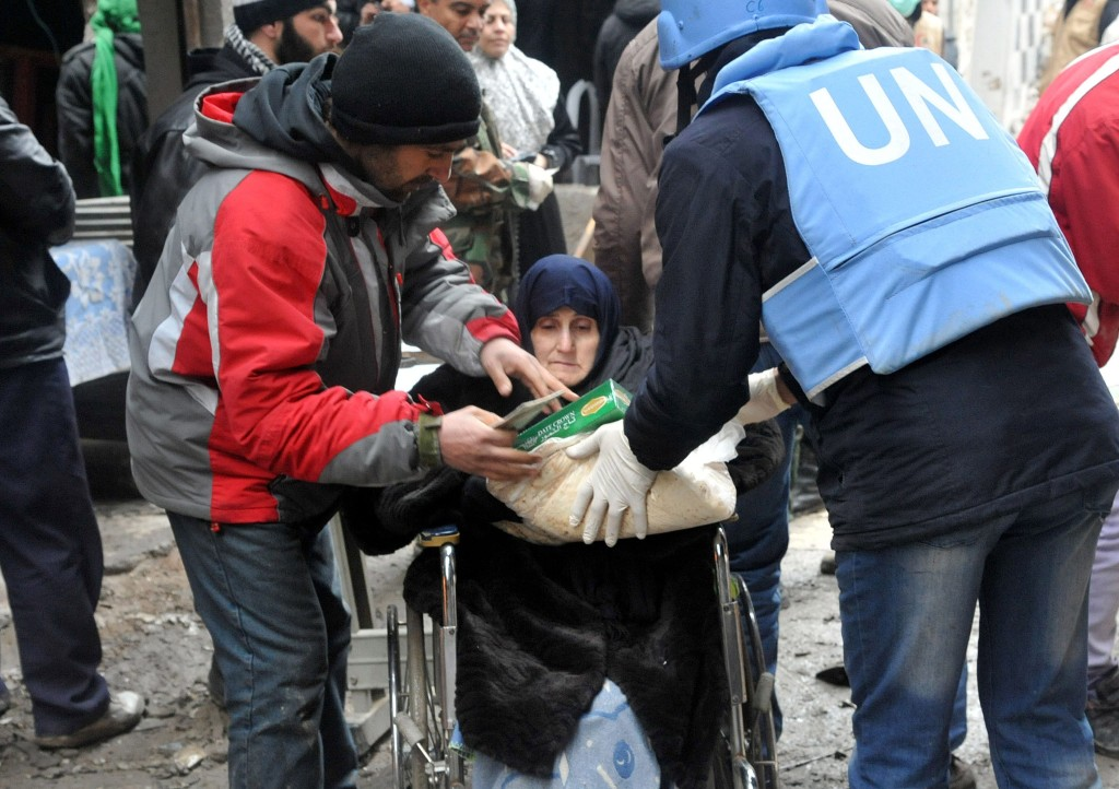 epa04055258 A handout photo released by Syria's official state news agency Syrian Arab News Agency (SANA) shows members of the United Nations Relief and Works Agency (UNRWA) distributing food parcels to residents of al-Yarmouk refugee Palestinian camp in Damascus, Syria, 04 February 2014. According to SANA, for the sixth day in a row, humanitarian aid continues to be distributed in al-Yarmouk Camp in Damascus with more people being evacuated for medical reasons. Over 4,300 food baskets have been distributed and 2,500 people with medical conditions have been evacuated.  EPA/SANA HANDOUT  HANDOUT EDITORIAL USE ONLY/NO SALES