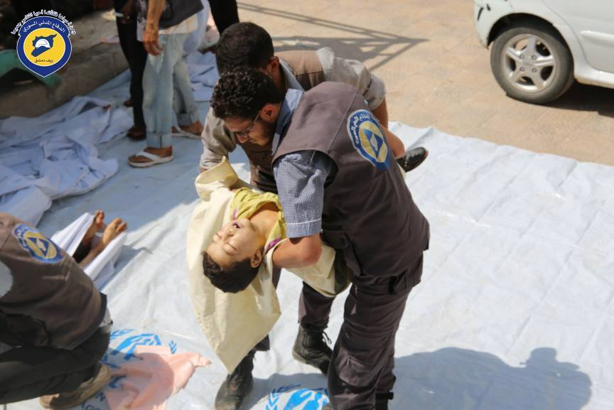 A member of the civil defence holds a child killed in the attacks on the city
