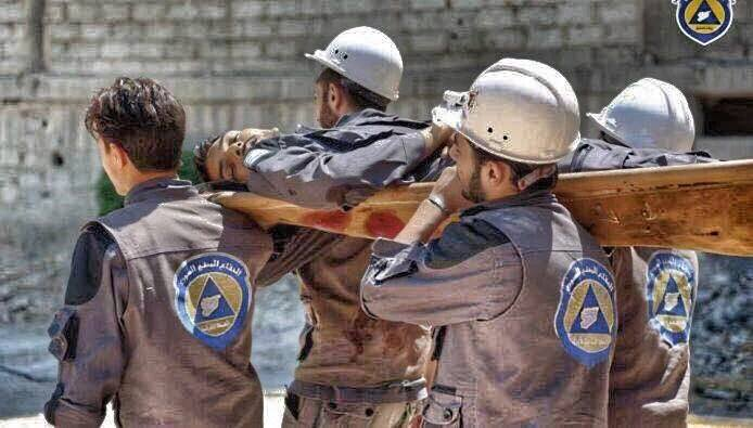 Members of the Civil Defence carry the body of a colleague killed in the attack
