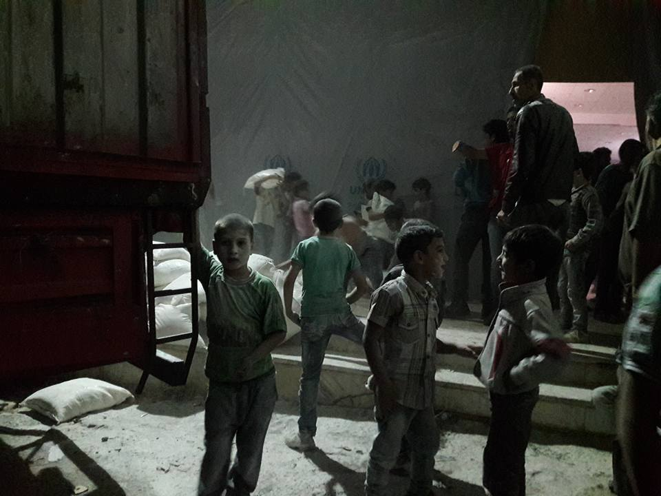 Children in Madaya assist with unloading items from the convoy