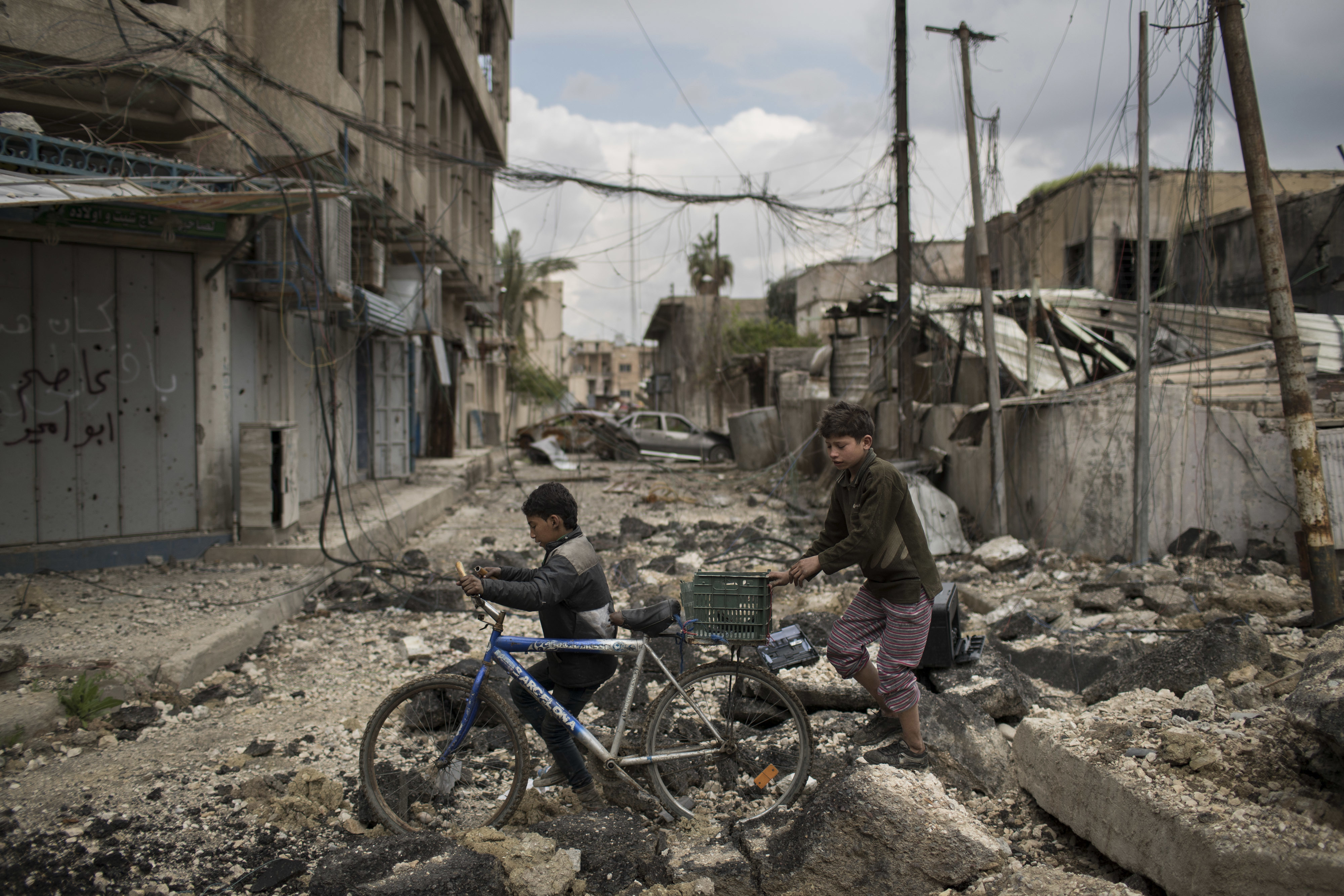 Iraqi boys walk on a destroyed street in a neighborhood recently retaken by Iraqi security forces during fighting against Islamic State militants on the western side of in Mosul, Iraq, Monday, April 3, 2017. (AP Photo/Felipe Dana)