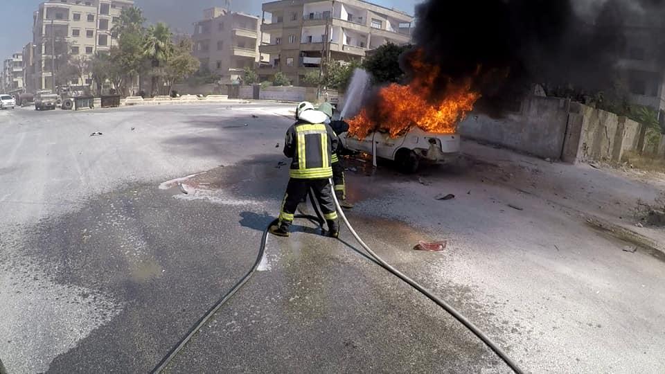 عناصر الدفاع المدني يقومون بإخماد الحريق الذي نشب في سيارة نتيجة لانفجار عبوة في إدلب